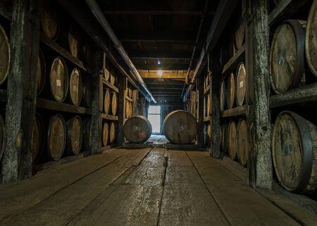 Walking Down Barrel Storage in Distillery in dim light 版權商用圖片