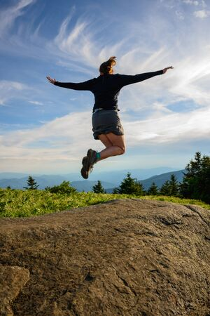 Leaping for Joy Against a Swirly Cloudy Sky in Blue Ridge mountains