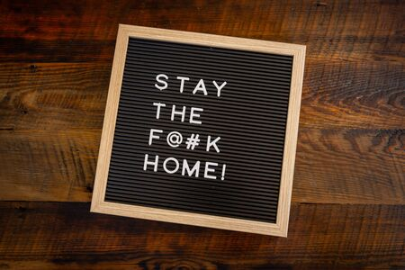 Stay the F@#k Home Message Centered on wooden background
