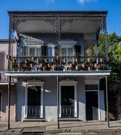 Flower Pots Hang from Balcony with wrought iron detail