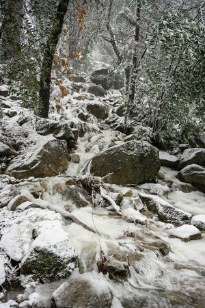 Water Rushes Through Snowy Boulders in Yosemite valley Stock Photo
