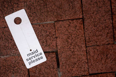 Maid Service Please hang sign on brick ground