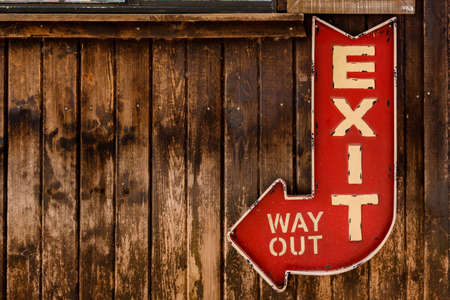 Red Exit Arrow on Wooden Wall with copy space