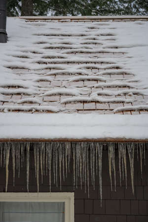 Snowy Roof and Icicles after snow has started melting and refrozen Reklamní fotografie