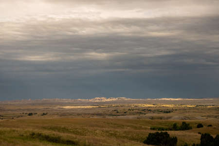 Light Patches Brighten Stormy Prairie in front of Badlands formations in South Dakota
