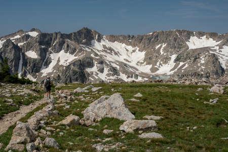 Woman Hikes Alongside Alpine Meadow High in the Teton range in summer