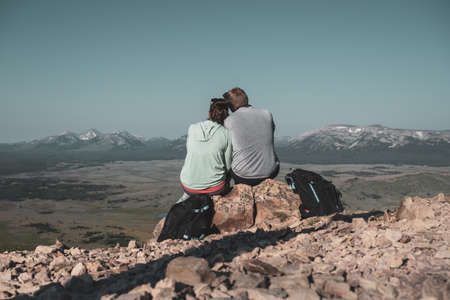 Couple looks out over hazy Wyoming mountains in Yellowstone