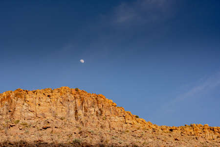 Moon Hangs In a Blue Sky Above Sunlit Orange Cliffs along the Grapevine Hills in Big Bend Standard-Bild