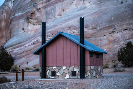 Pit Toilet At White House Campground In Southern Utah in front of tall rock wall