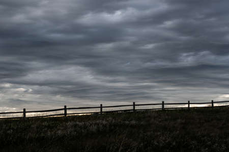 Split Rail Fence Silhouette With Gray Clouds Above in Badlands National Park
