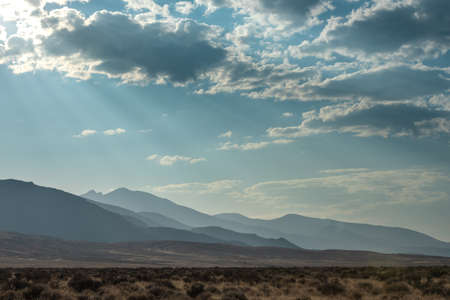 Sun Rays Break Through Clouds Over Great Basin national Park mountain layers