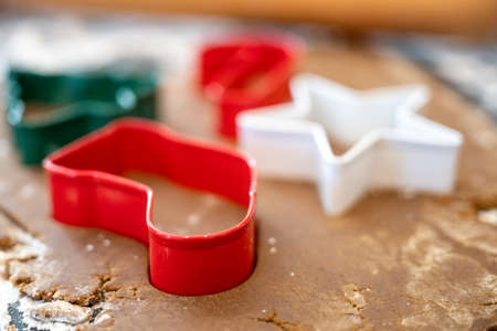 Red Stocking Cookie Cutter Pressed into Gingerbread Dough During Holiday Baking Session Stock Photo