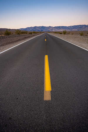 Freshly Painted Yellow Stripe Covers A Fading Stripe In The Middle of The Road in Death valley National Park Banco de Imagens