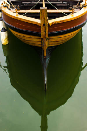 calm water: Wooden boat and its reflection in calm water