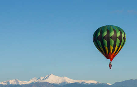longs peak: Hot Air Balloon in front of Mountains Stock Photo