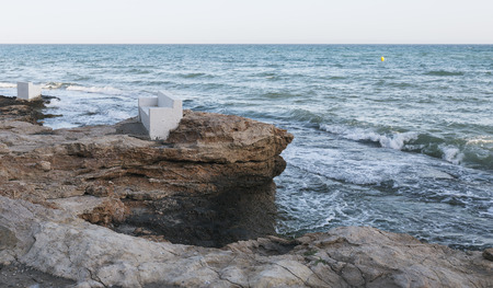 arises: Armchair on the rocks close to the sea Stock Photo