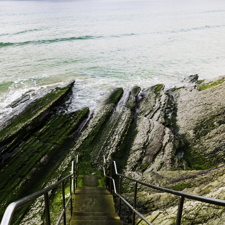 arises: Stairs with banister descending for the cliff towards the beach in San Sebastian