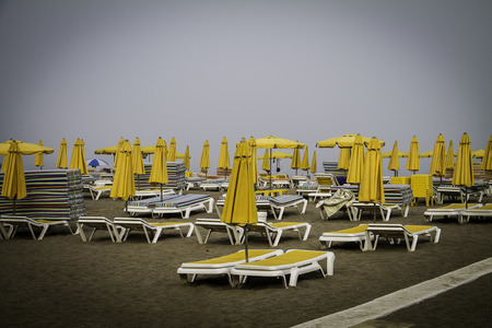 yelow: deckhcair and parasol yelow on the sea in a clouded day in Malaga. Spain Stock Photo