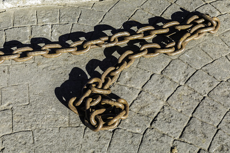briks: closeup old Rusty chain on the  pavement floor in sunny day