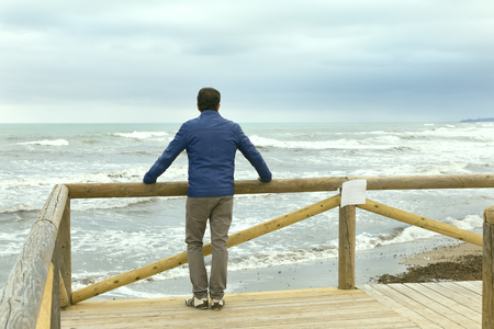 lonely men  with blue jacket looking at the mess sea Stock Photo