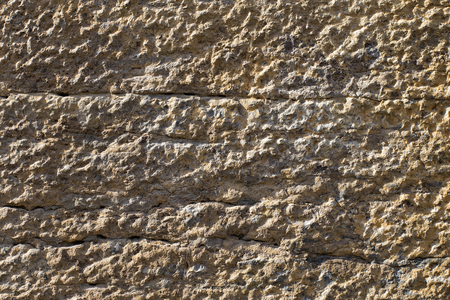 close up of a eroded texture of a beigh rough stone