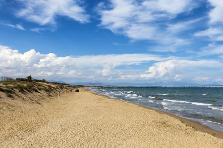 sandy seashore with dunes and clouds blue sky. Guardamar del Segura, Alicante, Spain