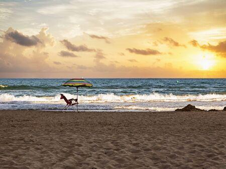 solitude striped  umbrella and chair  at the first beach line in Guardamar del Segura, Alicante. Spain