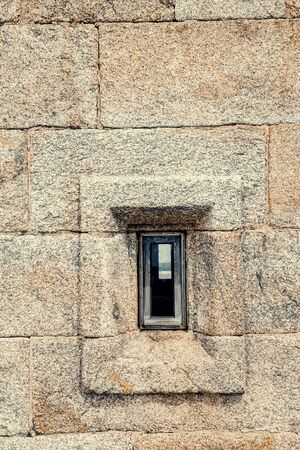 front view of granite stone wall with a small window
