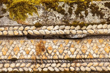 front view of stone wall with white pebbles, cement and moss Banco de Imagens
