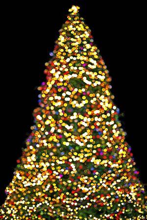 Fondo árbol de Navidad con luces multicolores que brillan intensamente en invierno Foto de archivo