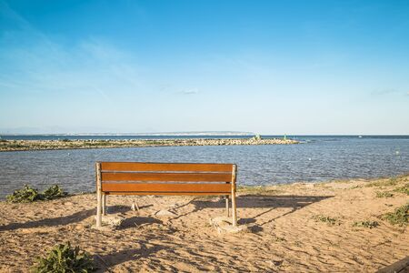 wooden bench for resting with views of sea at sunset. Alicante, Spain Zdjęcie Seryjne