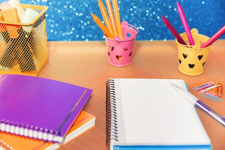close-up of multicolored containers with pencils and markers for drawing and writing in a notepad