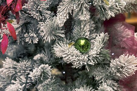 detail of bright green ball hanging on snowy christmas tree Stock Photo