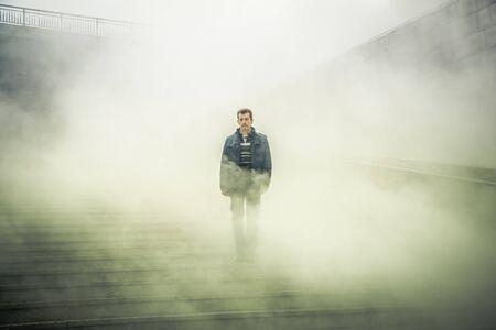 Hombre maduro, bajando las escaleras y a través de la niebla. Foto de archivo