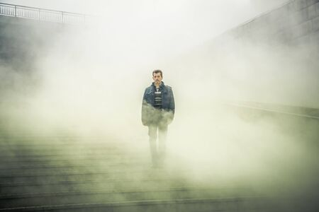 mature man walking down the stairs and through the fog