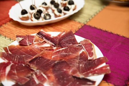 view of a white plate with messy slices of ham and appetizers with black olives Stok Fotoğraf