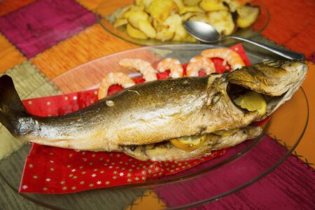 view of a home-cooked sea bass on a glass tray and a plate with baked potatoes