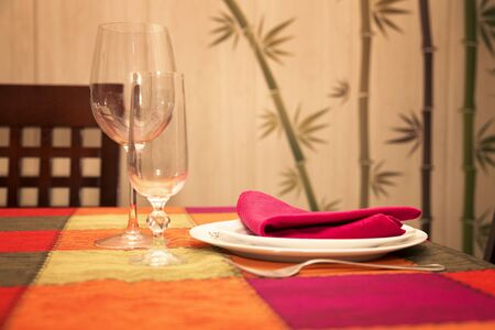 set service in a colorful table whit whit white dish and empty glasses