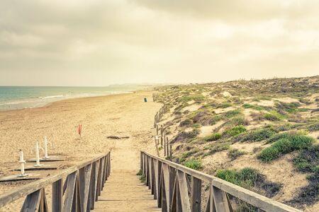 landscape of wooden footbridge to access the beach in summer . Guardamar, Alicante, Spain