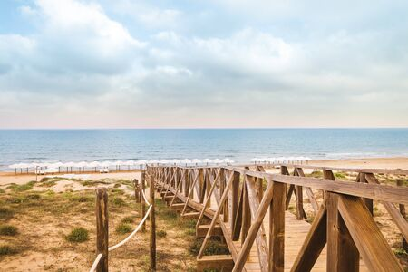 landscape of wooden pathway to access the beach in summer . Guardamar, Alicante, Spain