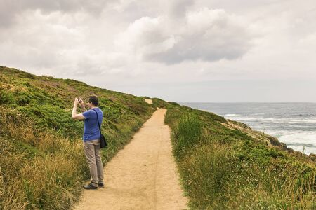 man in blue shirt on the edge of a long dirt road by the sea taking pictures with his smart phone