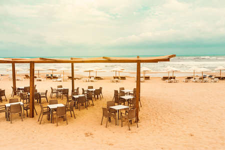 terrace bar with umbrellas on Guardamar beach at sunset Alicante. Spain