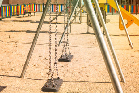 children's playground with empty swings suspended with steel chains