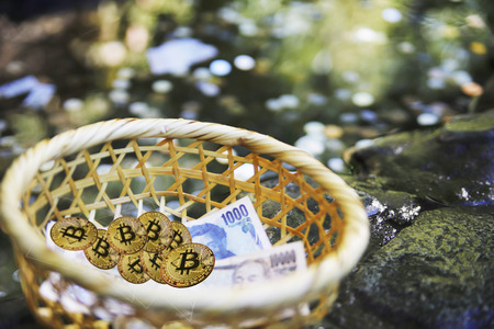 Close up of Gold Bitcoins and some Japanese Yens. , Japan - January 20, 2018