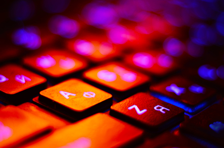 Close up. Blue backlight, backlit on laptop or keyborad computer of gaming in the dark. Computer laptop keyboard with Blue dark backlight, backlit in the dark. Concept computer.