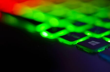 Laptop keyboard with blue backlight. Buttons closeup.