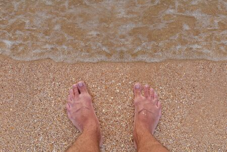 Mens feet stand on a sandy beach. Surf