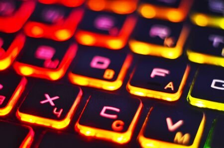 Laptop keyboard with red backlight. Buttons closeup.