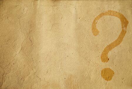 Sfondo. Punto interrogativo dipinto su una parete gialla. Marrone chiaro. Posto per il testo