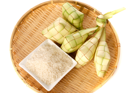 Ketupat (rice dumpling) and rice on traditional woven tray Stock Photo